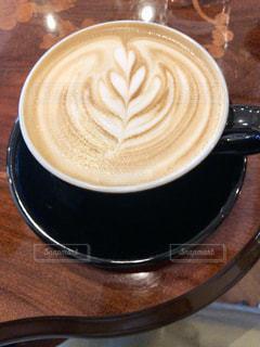 木製のテーブルの上に座っているコーヒー1杯の写真・画像素材[2281944]