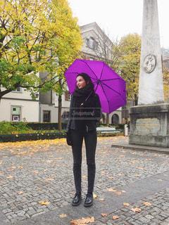傘を保持している歩道上に立っている女性の写真・画像素材[1226404]
