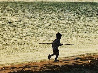 水の横にあるビーチの上を歩く男の写真・画像素材[1173428]