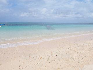 海の横にある砂浜のビーチの上に立っている人の写真・画像素材[1202300]
