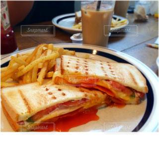 サンドイッチとフライをテーブル上プレートの写真・画像素材[1174522]