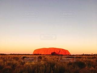 ウルルを背景にした乾燥した草原に沈む夕日の写真・画像素材[2904994]