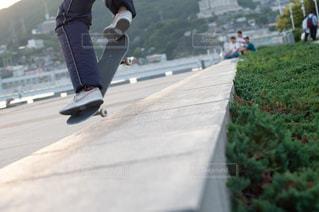 道路の側をスケート ボードに乗って男の写真・画像素材[1251494]