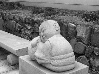 レンガの壁の前に座っている人の写真・画像素材[1211846]