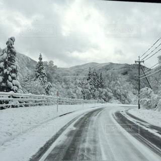 背景の山と雪の覆われた道路の写真・画像素材[1677532]