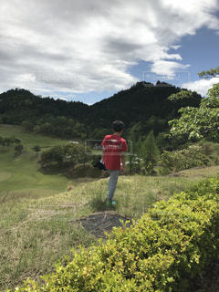 草で覆われた丘の上に立っている人の写真・画像素材[1184544]