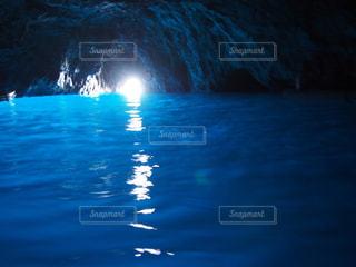 背景の青の洞窟の水の体の前に明るい光の写真・画像素材[1194728]