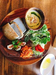 木製のテーブルの上に食べ物のプレートの写真・画像素材[1287021]