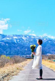 山の道の側面をスケート ボードに乗って男の写真・画像素材[1287023]