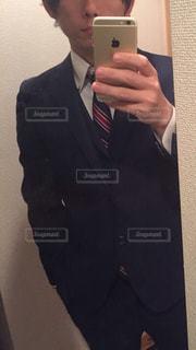 カメラにポーズ鏡の前に立っている男の写真・画像素材[1850386]