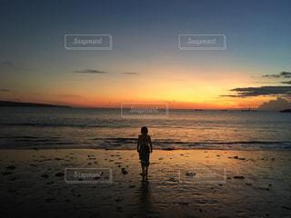 バック グラウンドで夕焼けのビーチに立っている人の写真・画像素材[1198617]