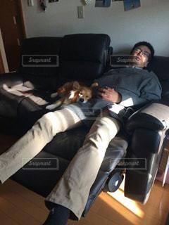 ソファで横になっている人の写真・画像素材[1212669]