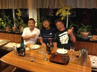ワイングラスとテーブルに座っている人のグループの写真・画像素材[1191595]