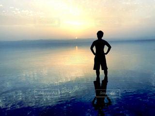 バック グラウンドで夕日を持つ男の写真・画像素材[1273073]