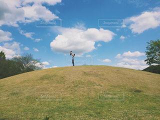 緑豊かな緑のフィールドに立っている人の写真・画像素材[1198480]