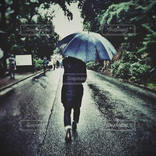 傘を持って雨の中を歩く女性の写真・画像素材[1216536]