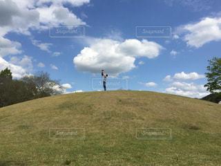 草で覆われた丘の上に立っている人の写真・画像素材[1247645]