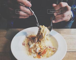 フォークで皿の料理とテーブルに座って人の写真・画像素材[1271073]