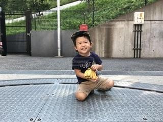歩道の上に座っている若い男の子の写真・画像素材[1371261]
