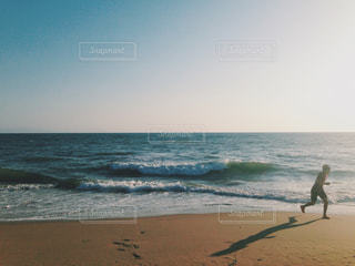 海の横にある砂浜のビーチの上に立っている人の写真・画像素材[1386836]
