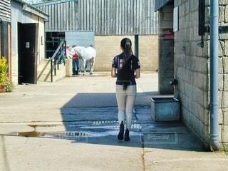 建物の隣に歩道を歩く女性の写真・画像素材[1242518]