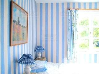 ウィンドウの横にある寝室の青と白のベッドの写真・画像素材[1261654]