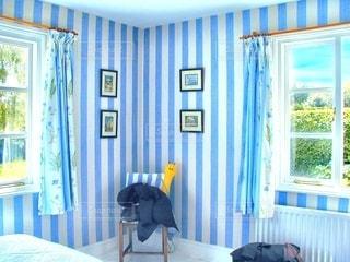 寝室、ベッドと窓の前の椅子の写真・画像素材[1265853]