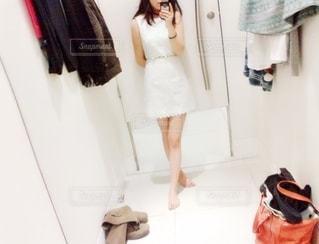 カメラにポーズ鏡の前に立っている女性の写真・画像素材[1657605]