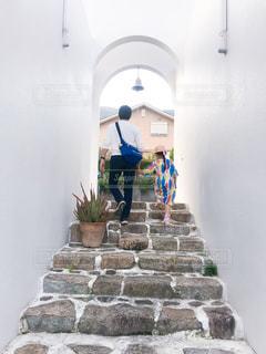 レンガの壁の横に立っている人の写真・画像素材[2207476]