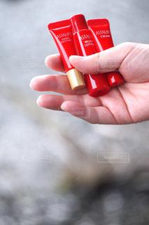 赤いオブジェクトを持っている手の写真・画像素材[763290]