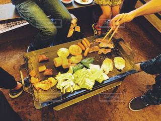食物と一緒にテーブルに座っている人々 のグループの写真・画像素材[1204400]