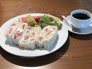 コーヒー カップの横にある皿の上のケーキの一部の写真・画像素材[1270844]