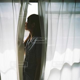 窓の前に立っている人の写真・画像素材[2168935]