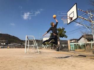 バスケット ボールのコート上でのトリックをしている男の写真・画像素材[1323854]