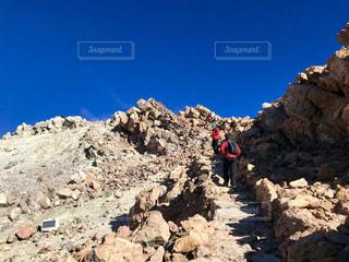 岩が多い丘の上に立っている人の写真・画像素材[1414466]