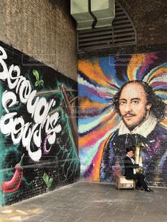 落書きで覆われた壁の隣に立っている男の写真・画像素材[2230614]