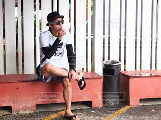 携帯電話で話しているベンチに座っている人の写真・画像素材[1264272]