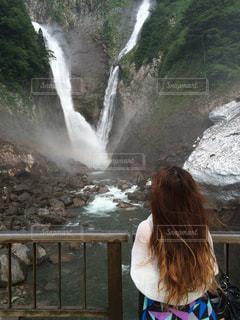 滝の隣に立っている人の写真・画像素材[1264287]