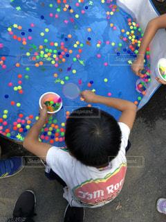 小さな子供を抱いた手がカメラを見ているの写真・画像素材[2462126]