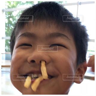 フライドポテトを口と鼻で食べる息子の写真・画像素材[1374624]