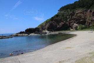 水の体の横にある岩のビーチの写真・画像素材[1400121]