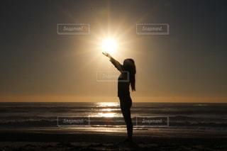 夕日を背景にビーチに立っている人の写真・画像素材[3397728]