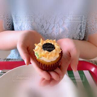 女性,食べ物,スイーツ,ケーキ,ひまわり,女性の手,手持ち,デザート,カップケーキ,人物,人,ポートレート,マフィン,ライフスタイル,手元,ペストリー