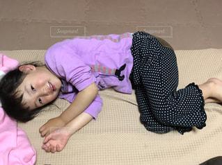 座布団上で横になっている少女の写真・画像素材[1215861]