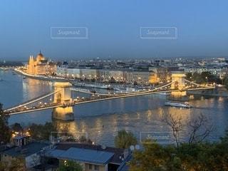 都市を背景にした水域に架かるチェーンブリッジの写真・画像素材[2722332]