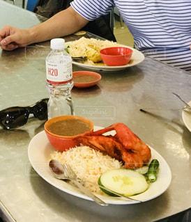 食べ物の皿を持ってテーブルに座っている人の写真・画像素材[2765572]