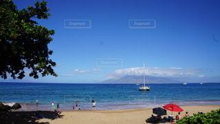 水の体の近くのビーチの人々 のグループの写真・画像素材[1216286]