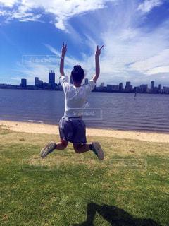 青空にジャンプする女の子の写真・画像素材[1222034]