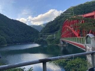 背景の山が付いている水の体の上の橋の写真・画像素材[1429606]