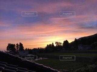 芝生のフィールドに沈む夕日の写真・画像素材[1405212]